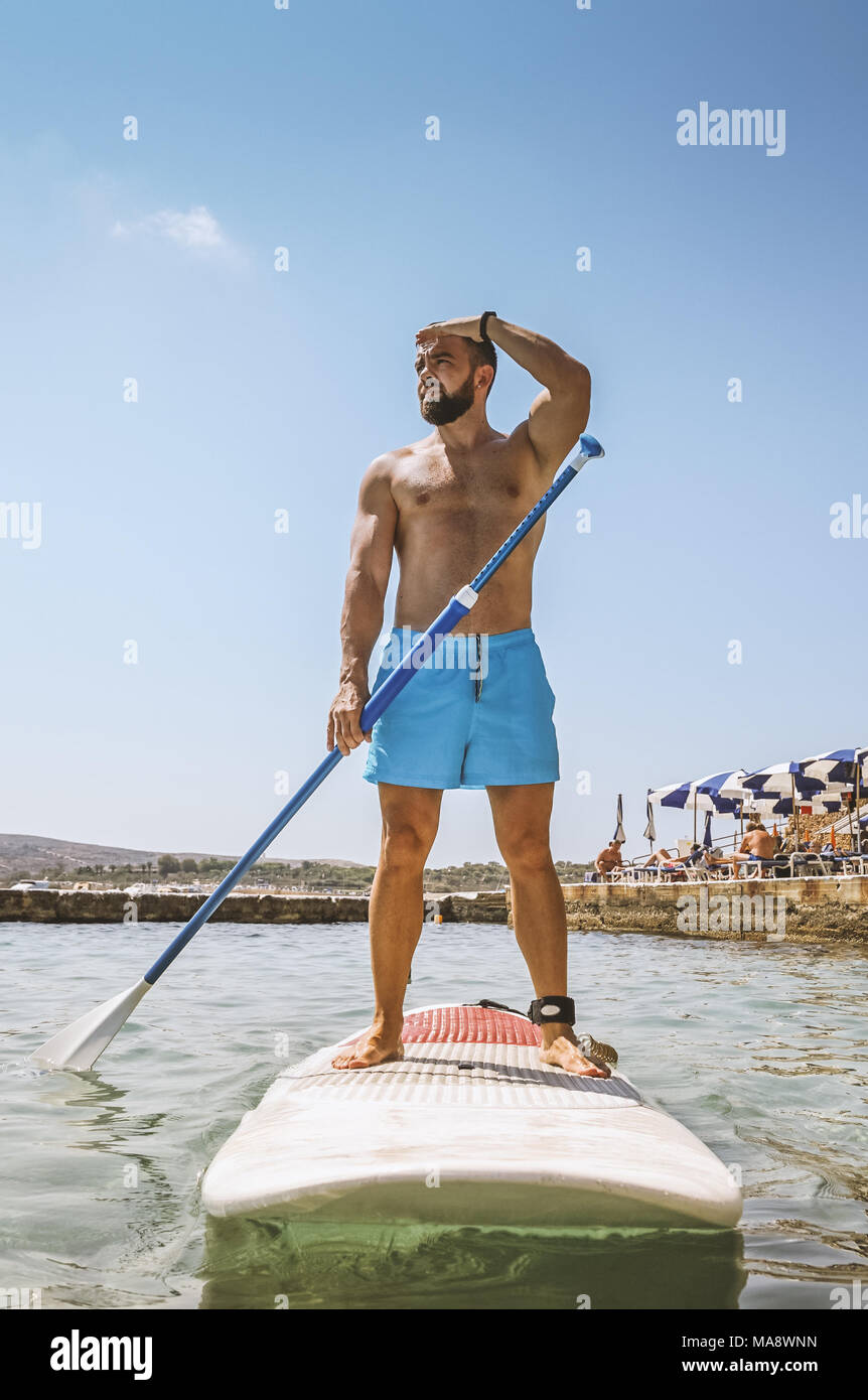 Man adult bearded Surfer stand up on paddle board on sea. Summer active vacation and water sport concept - Stock Image