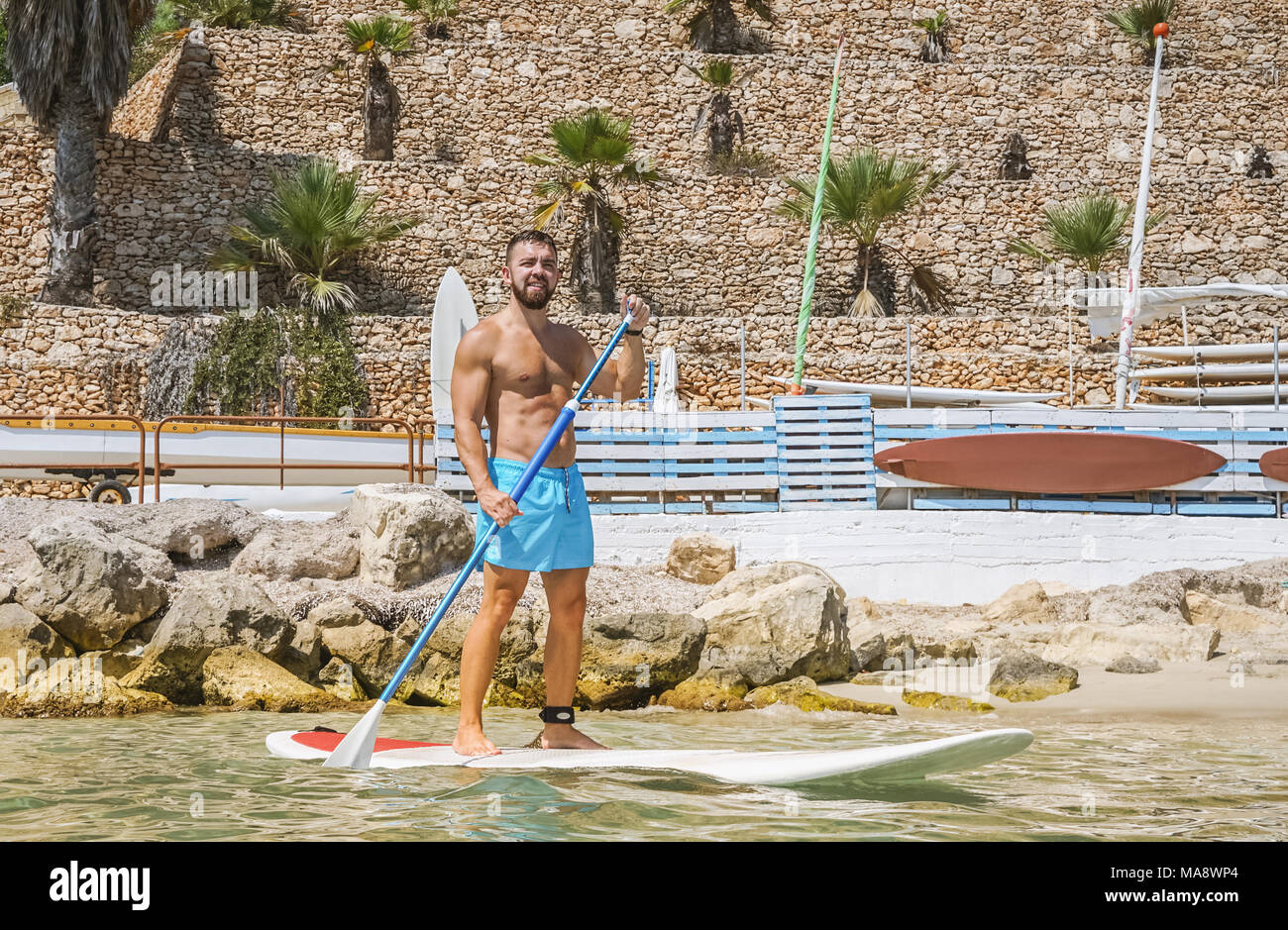 Paddleboard beach man stand up on paddle board and learns surfing. Summer active vacation and water sport concept - Stock Image