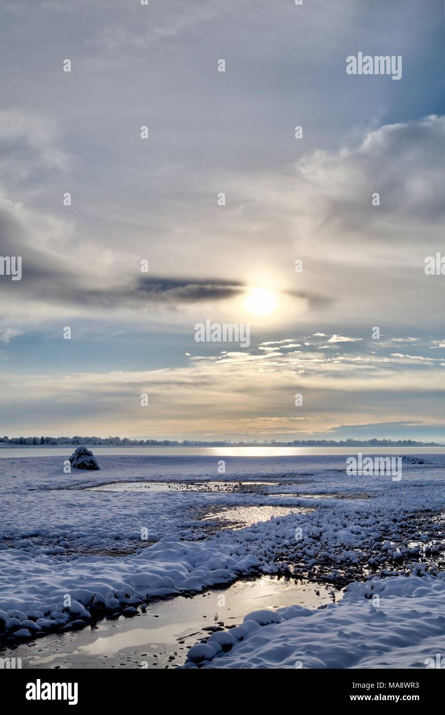 Early morning sunlight is filtered by clouds and is reflected in small pools of water in a snow covered catch basin - Stock Image