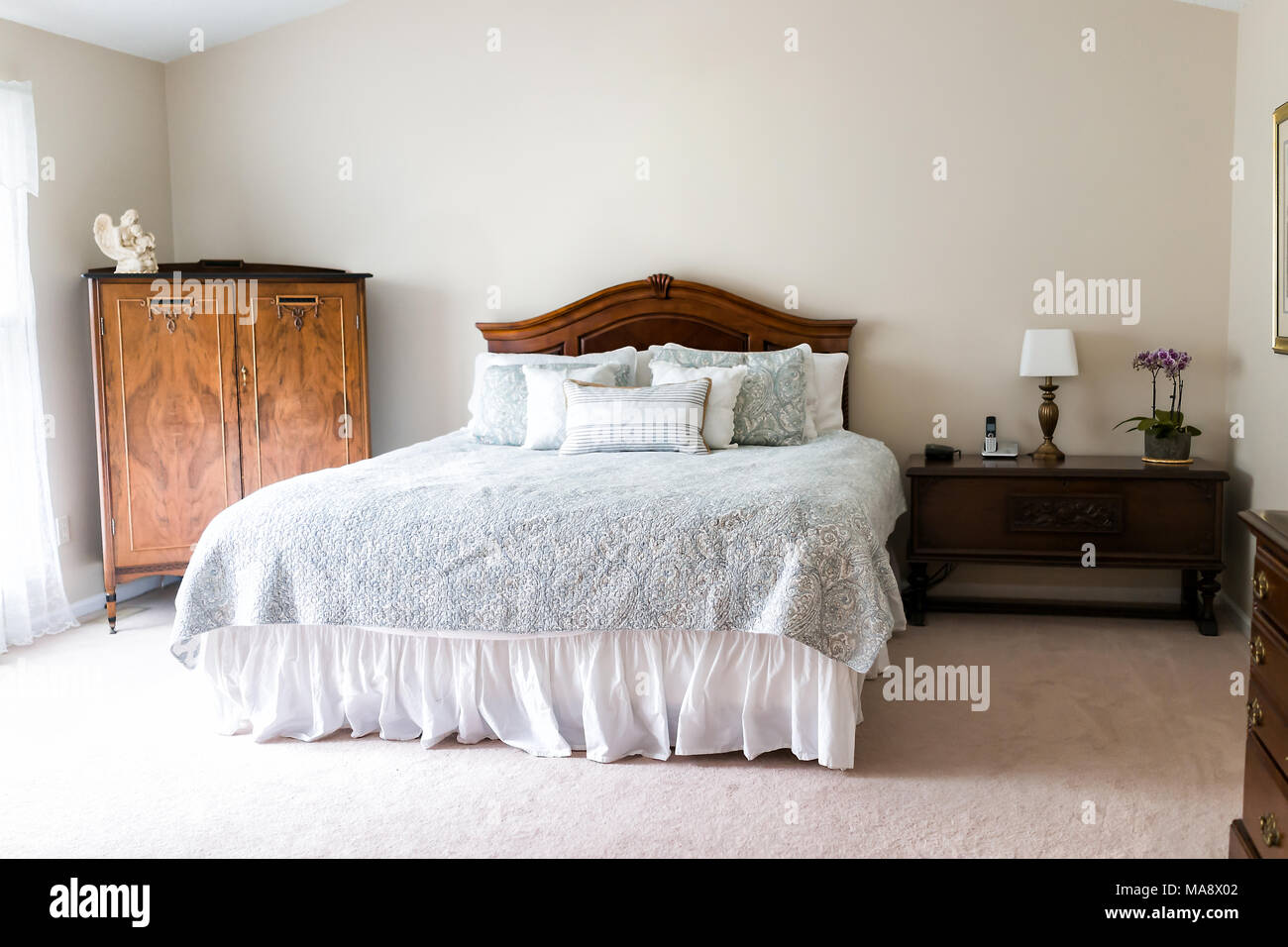 Closeup of new bed with headboard, decorative pillows, comforter, in ...