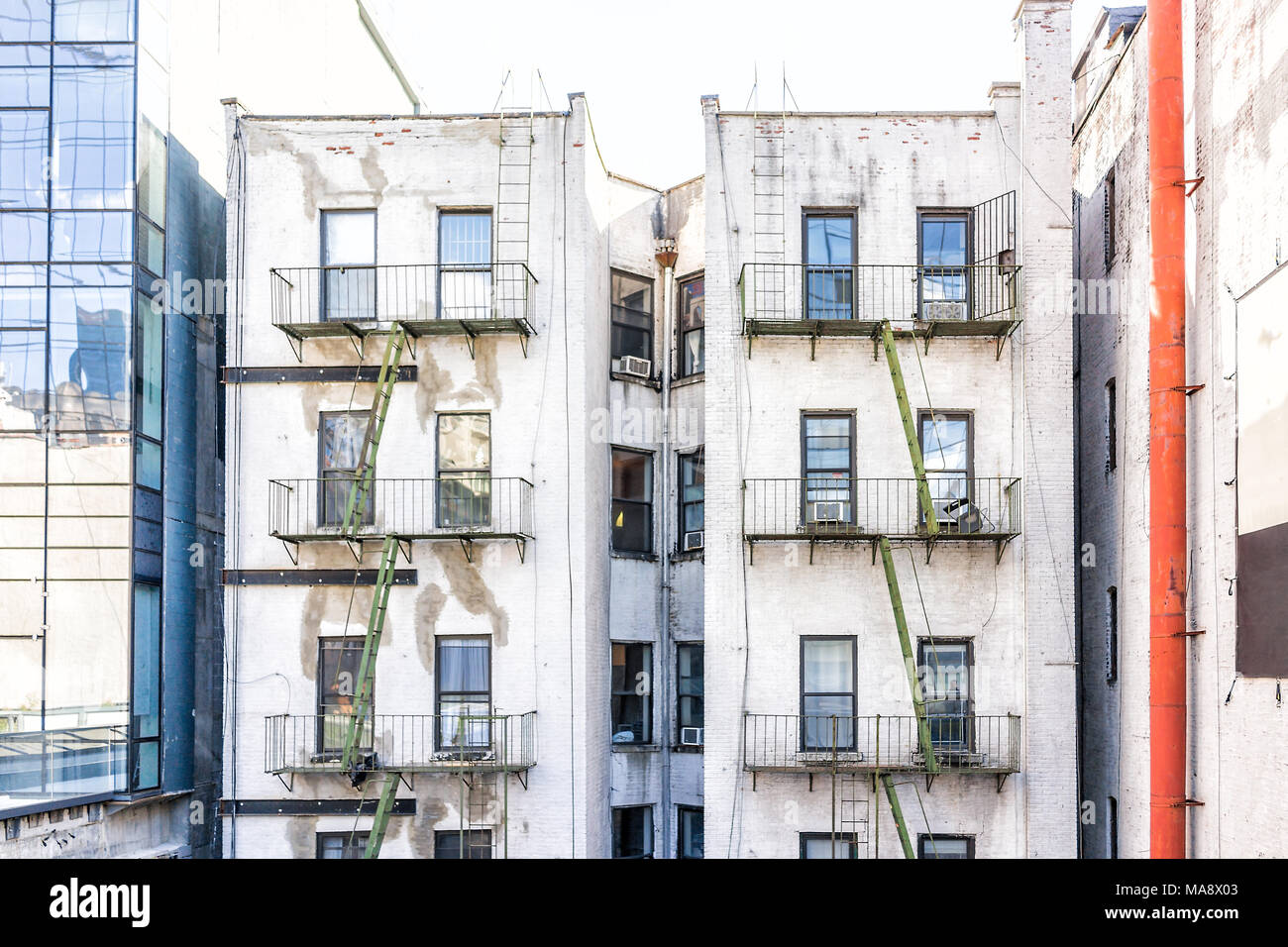 Old Apartment Condo Building Exterior Architecture In Chelsea, NYC,  Manhattan, New York City With Fire Escapes, Windows, Green Ladders