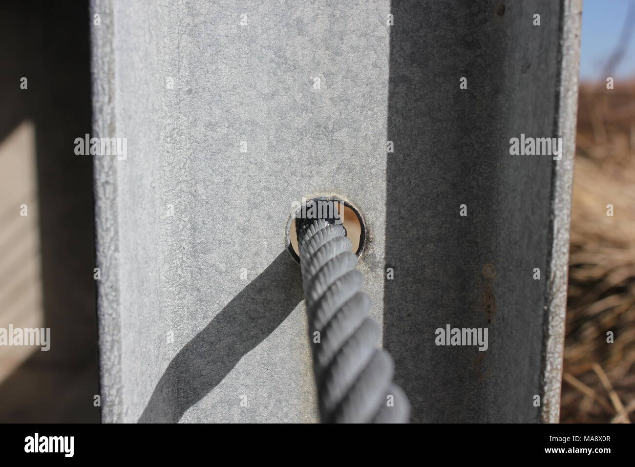 Architectural and structural detail of a steel code threading a steel ibeam column. - Stock Image