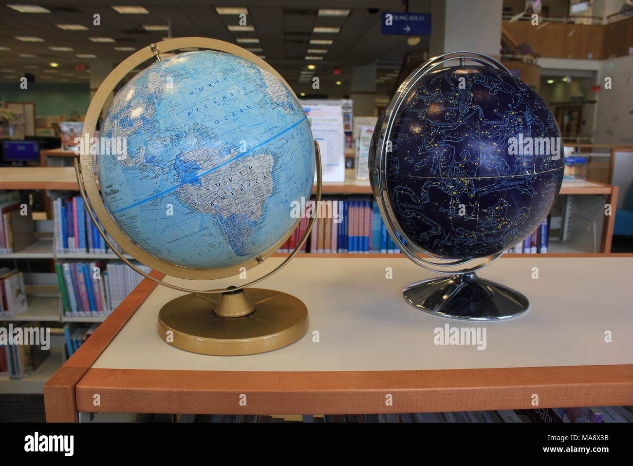 Two large globes - one earth and one sky / celestial / star system - placed on top of a bookcase at the local public library's children's department. - Stock Image