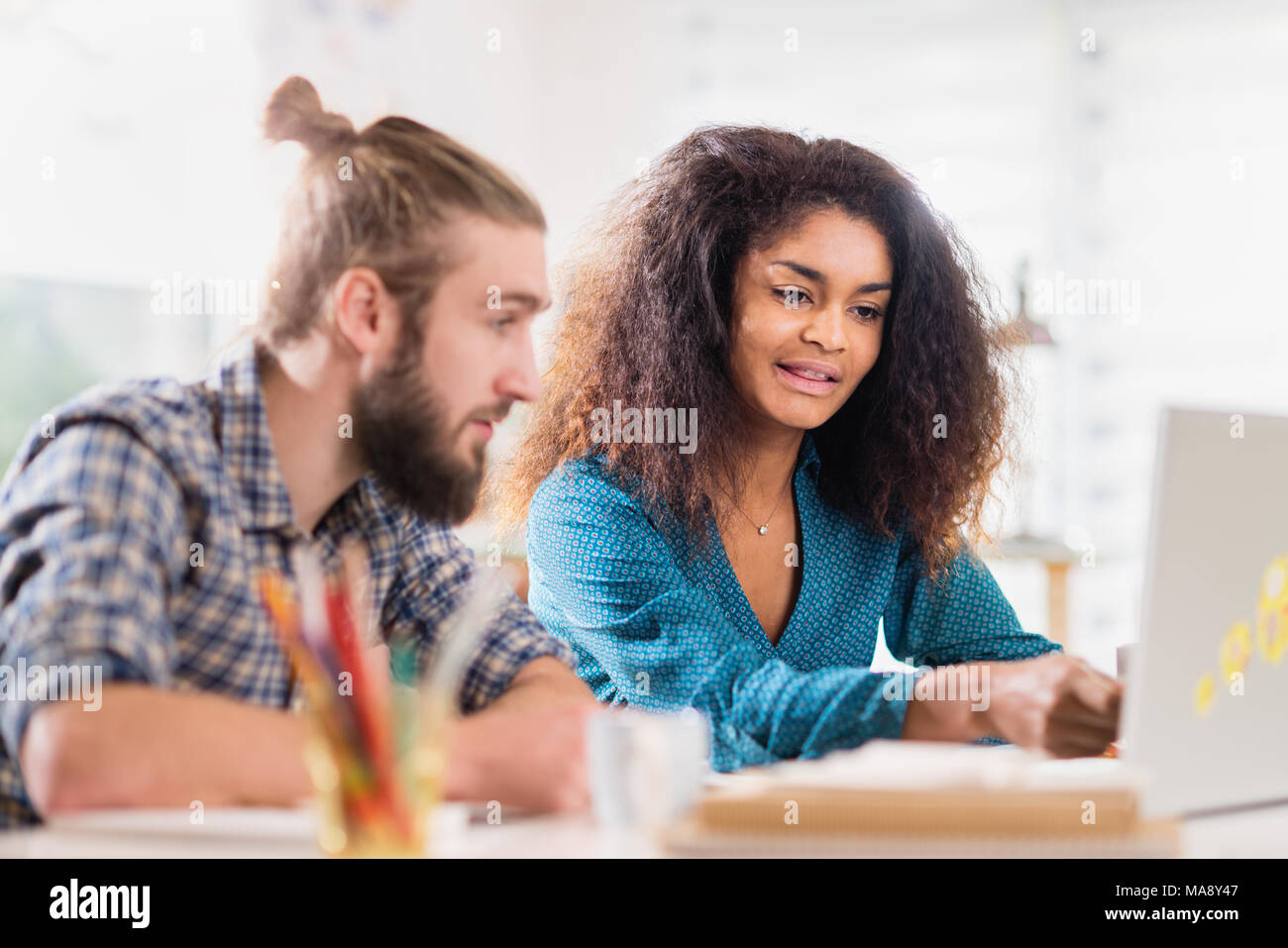At office creative team at work. A young black woman shares  ide - Stock Image