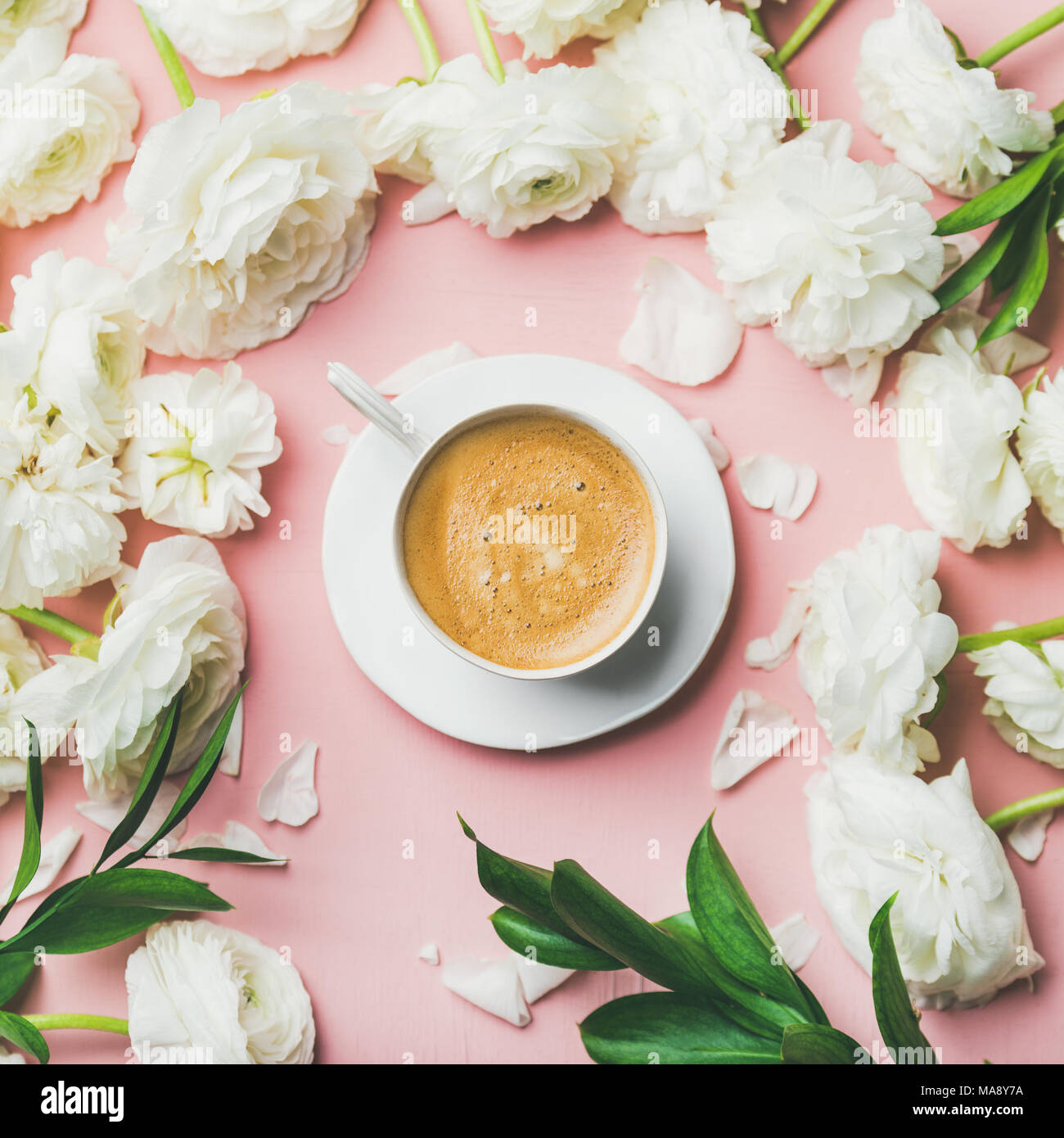 Cup of coffee and ranunculus flowers on light pink background Stock Photo