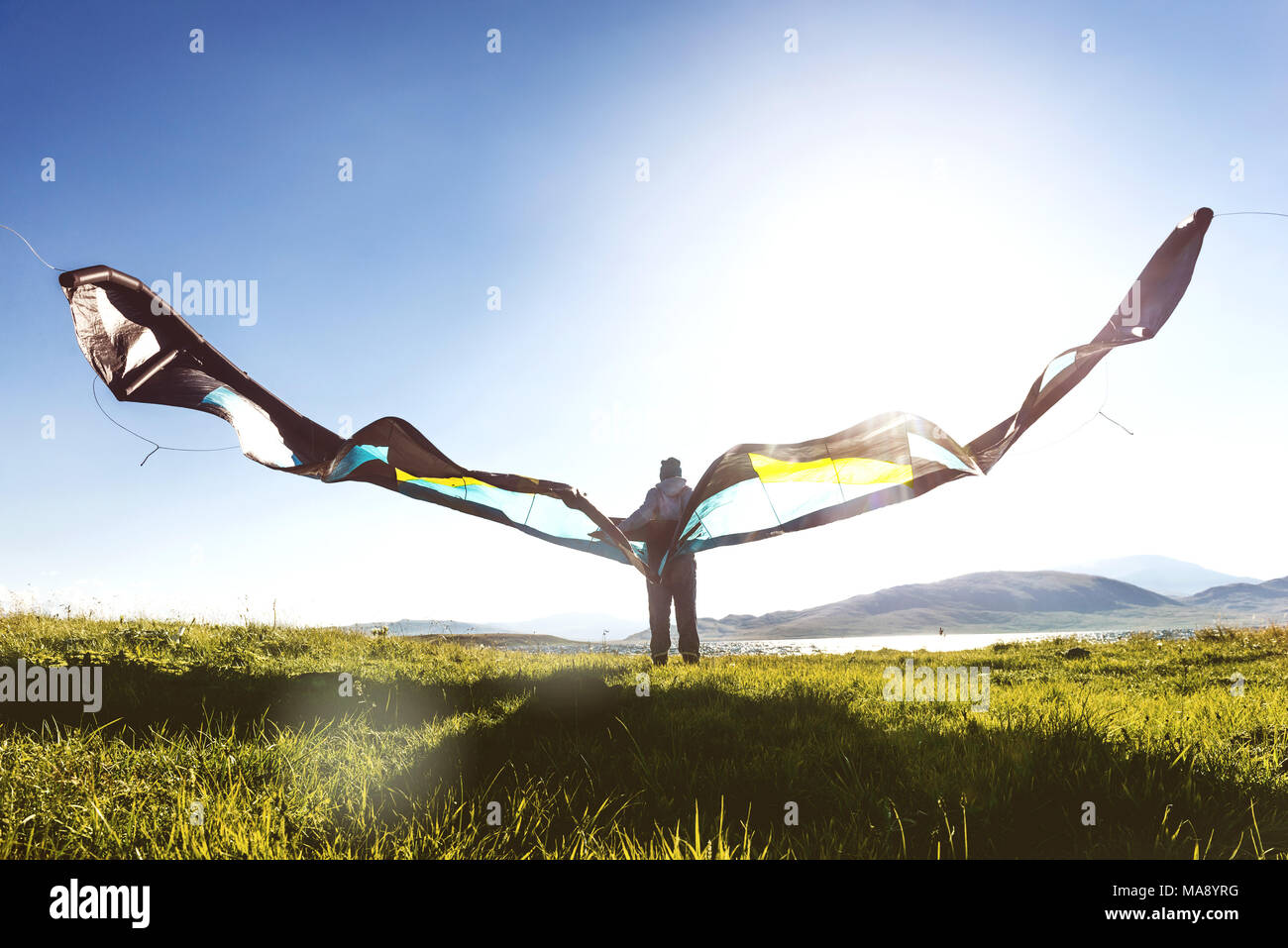 Man woman stands with kite in sun light - Stock Image