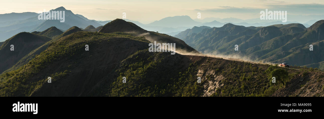Travelling South America by 4x4, aerial panorama of our Mitsubishi pick-up driving over the crest of beautiful green hills followed by a dust cloud tr - Stock Image