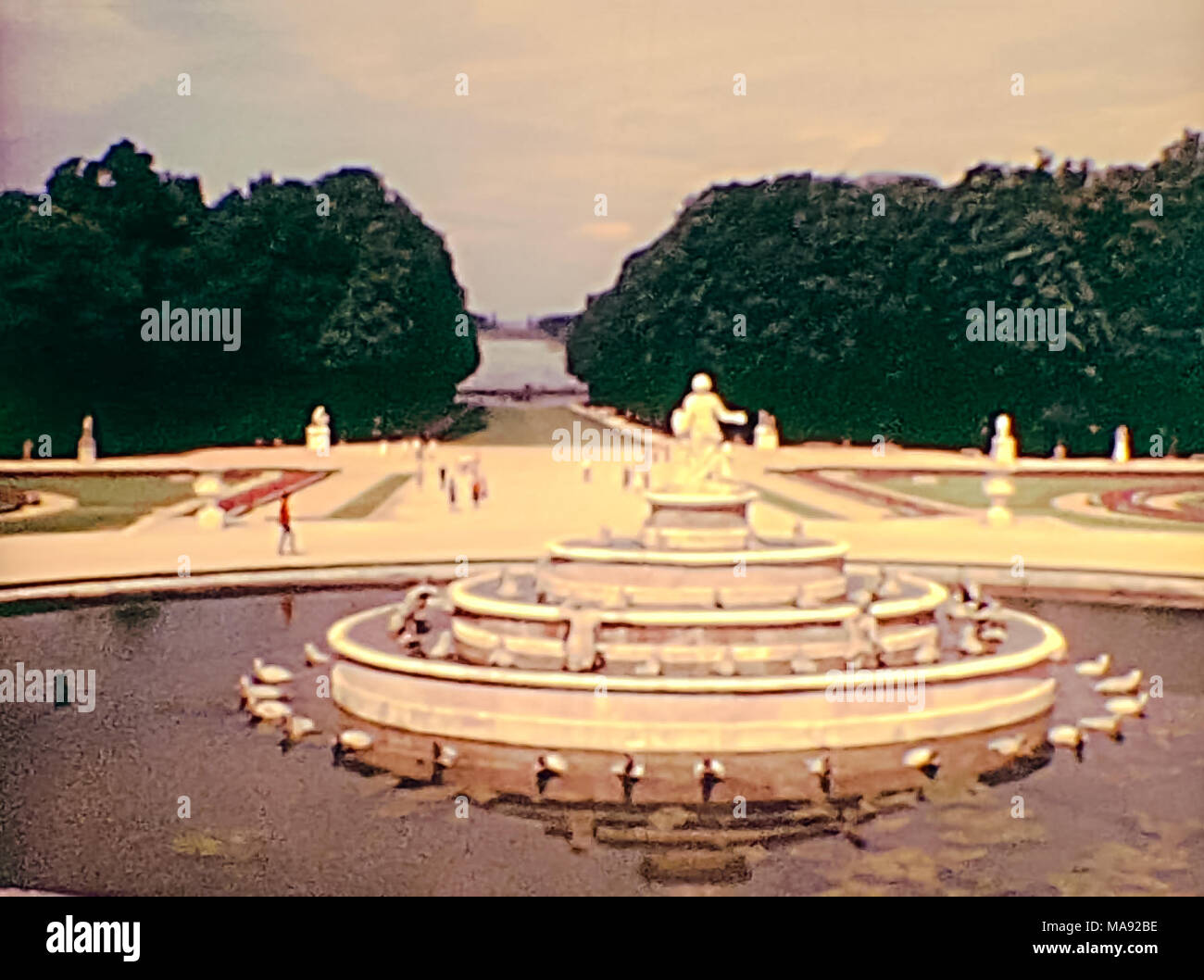 Fountain in the gardens of the Parisian Palace of Versailles with tourists in 1976. Historic archival footage in Paris city of France in 1970s. - Stock Image