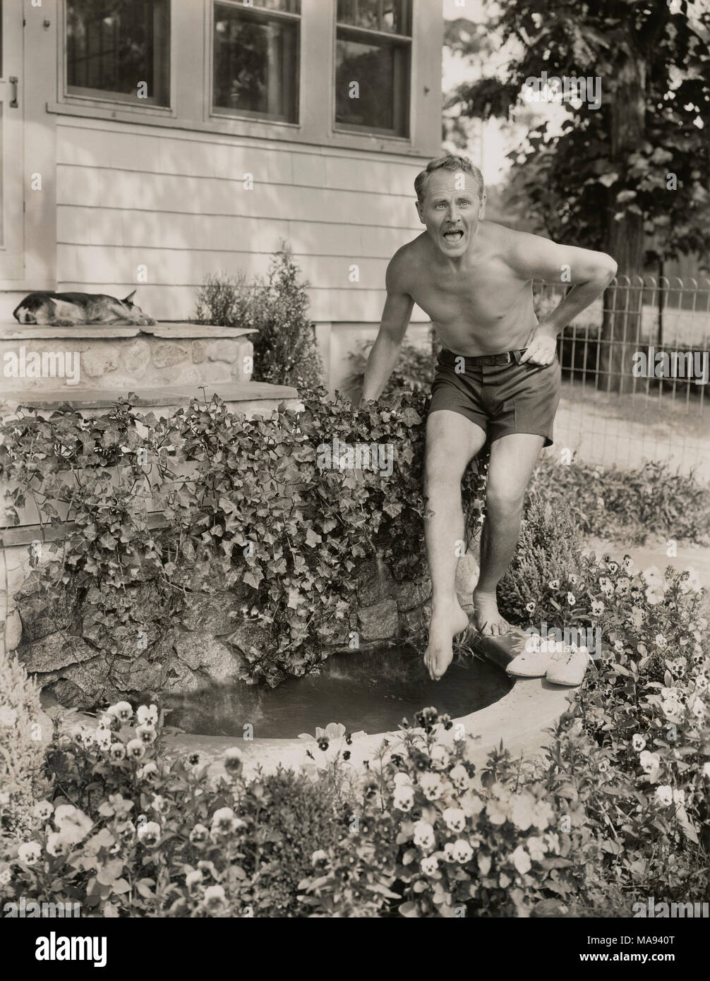 Charles Ruggles, Publicity Portrait Testing the Water of Aquarium at his Home, East Setauket, New York, USA, by Shalitt for Paramount Pictures, 1930's - Stock Image