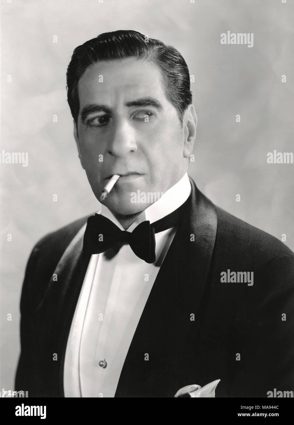 Actor Robert Warwick, Head and Shoulders Publicity Portrait Wearing Tuxedo and Smoking Cigarette, 1930's - Stock Image