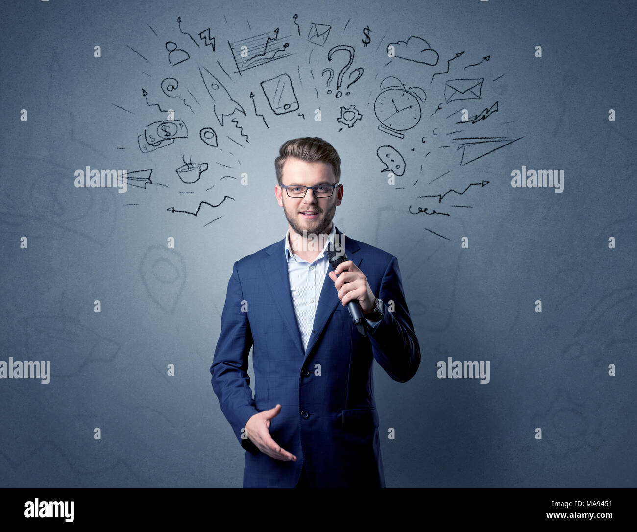 Businessman speaking into microphone with mixed doodles over his head Stock Photo
