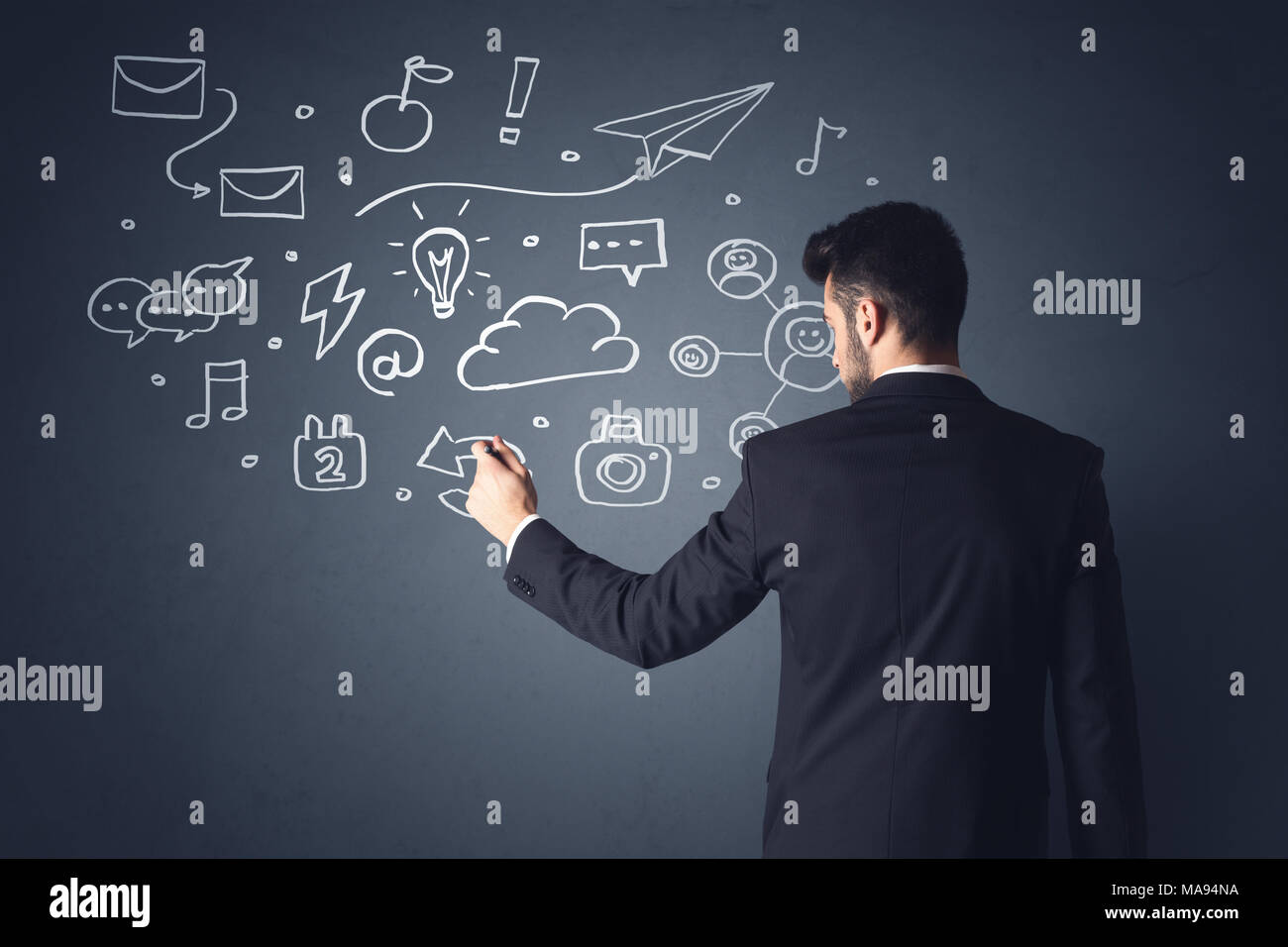 Young businessman in black suit standing in front of white mixed media icons - Stock Image