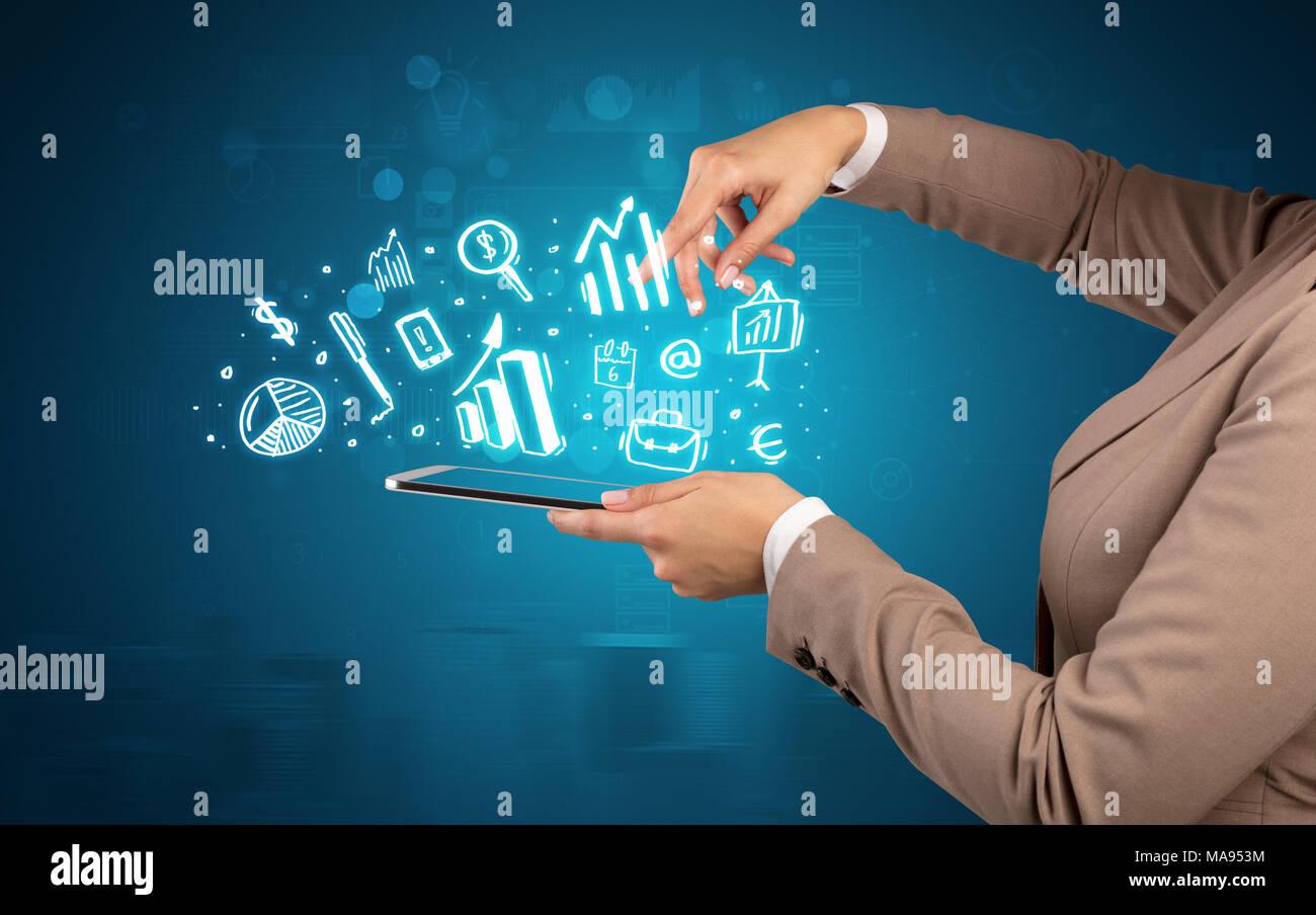 Elegant hand holding tablet with chalk drawn social media symbols above  - Stock Image