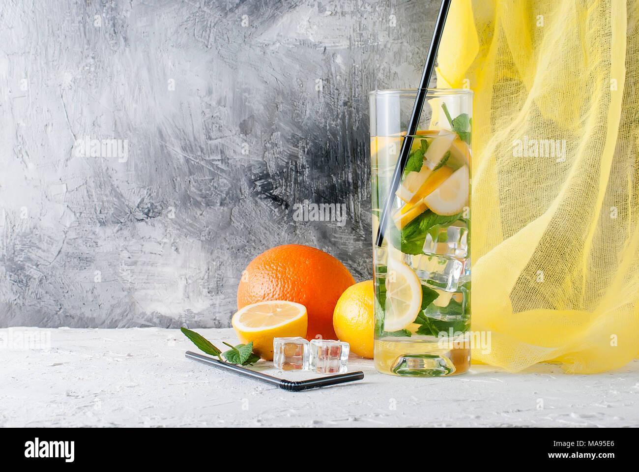 Fresh homemade lemonade in glass with lemon, orange, ice and mint. Ingredients for lemonade. - Stock Image