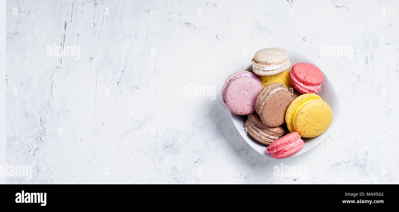 cup of coffee with milk and colorful makaoouns on a light background. Top view. Banner. Copy space. - Stock Image