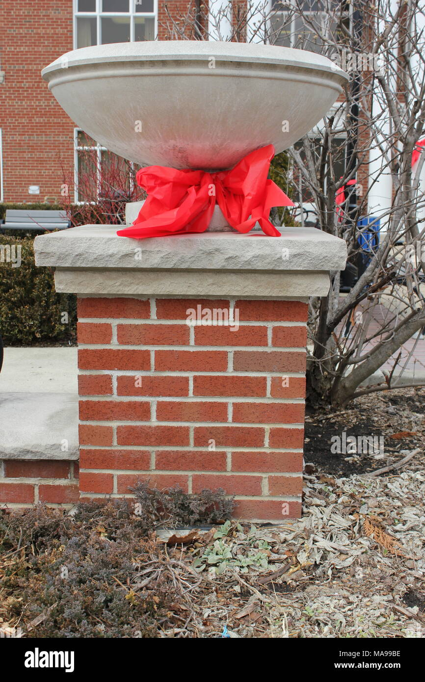 Huge red plastic ribbon tied around a beautiful pillar memorializing the death of a local firefighter. - Stock Image