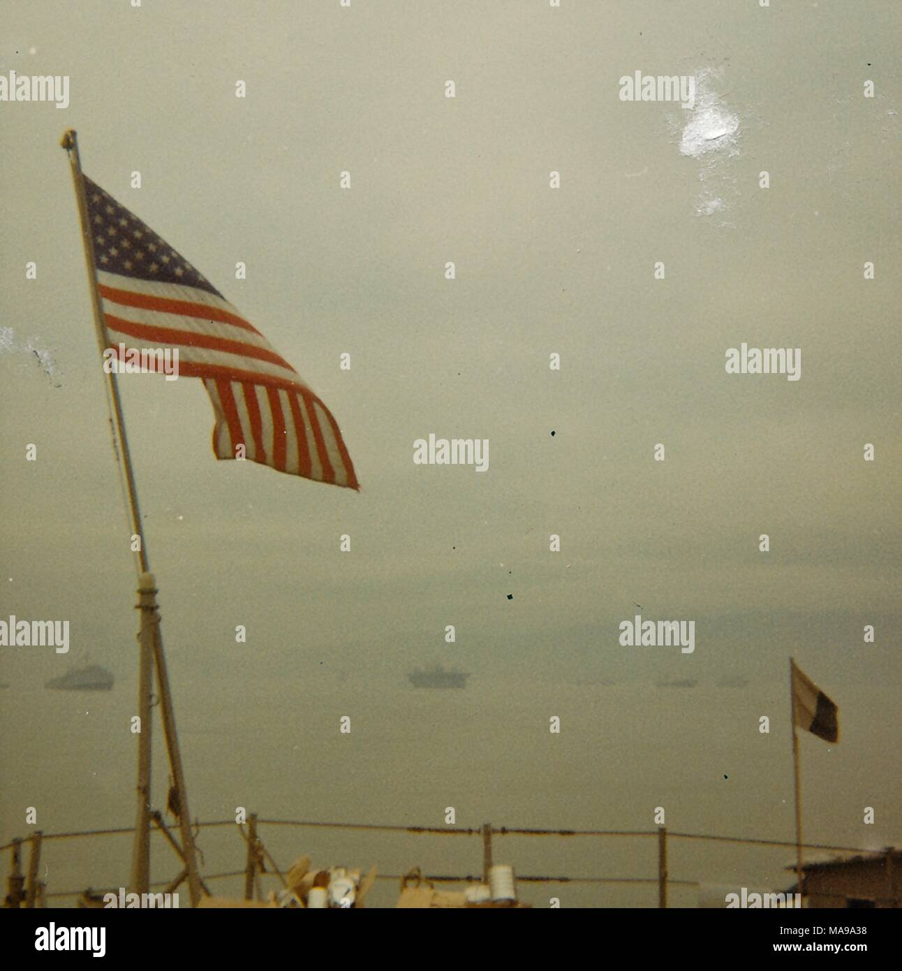Color photograph, showing a US flag, flying from the deck of a ship, with several battleships and a hazy coastline in the background, photographed in Vietnam during the Vietnam War, 1968. () - Stock Image
