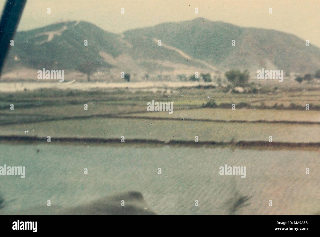 Color photograph, shot from inside a vehicle, showing a flat expanse of rice paddies, with mountains in the distance, photographed in Vietnam during the Vietnam War, 1968. () - Stock Image
