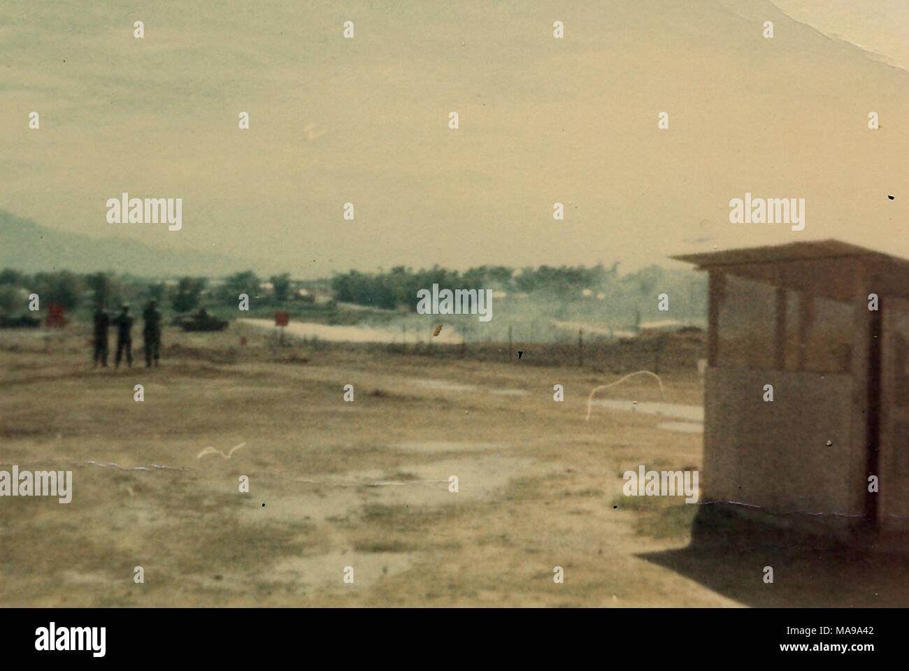 Color photograph showing a guard post at the right of a muddy field, with three figures (presumably soldiers) flags, and a tank in the distance, photographed in Vietnam during the Vietnam War, 1968. () - Stock Image