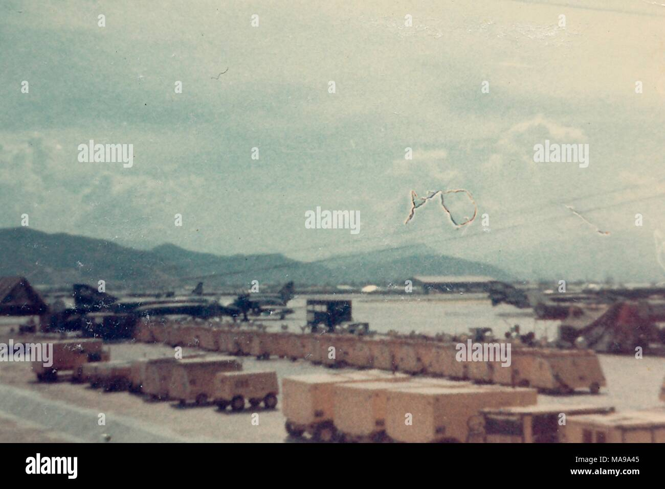 Color photograph, showing several rows of supplies or shipping containers, and a number of airplanes docked on an airstrip, with mountains in the background, photographed in Vietnam during the Vietnam War, 1968. () - Stock Image