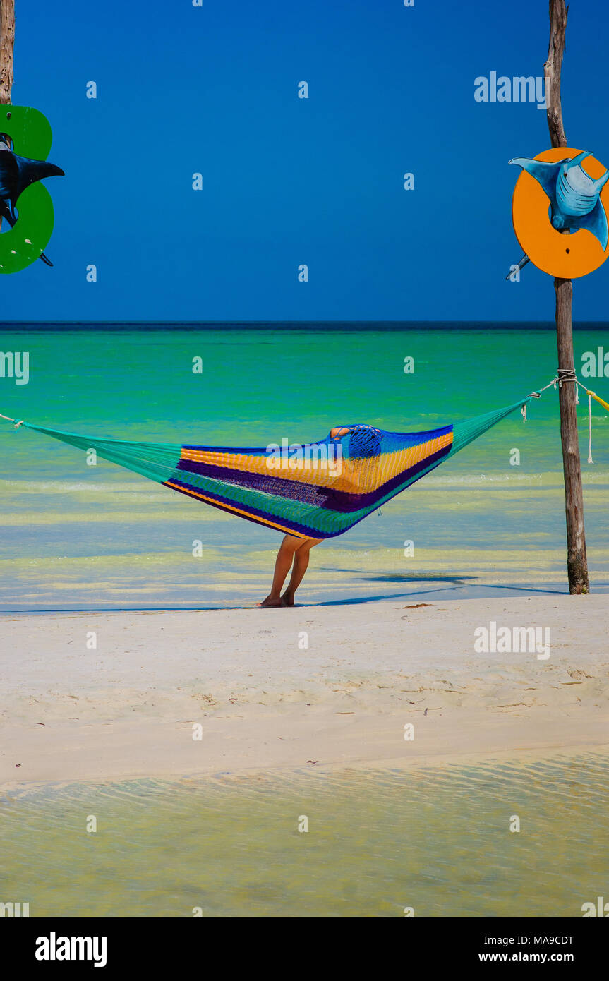 Woman relaxing in an hammock on the beach in Holbox, Mexico - Stock Image