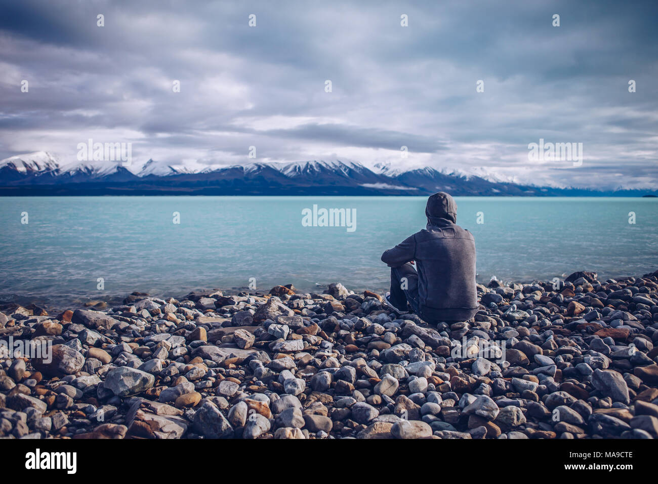 Young man looking out over Lake Tekapo and snow capped mountains in New Zealand Stock Photo