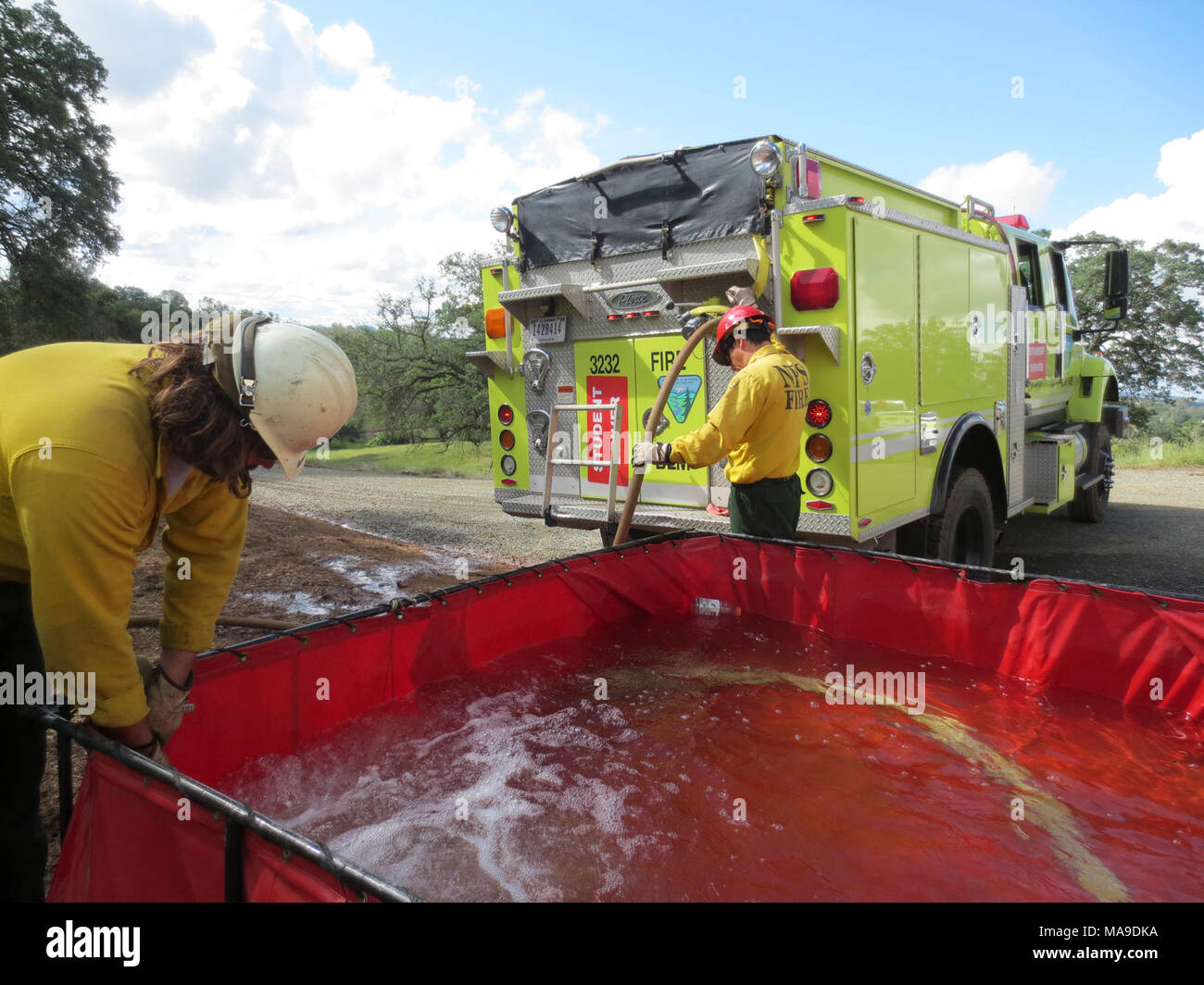 Portable Water Tank  Wildland firefighters fill a large