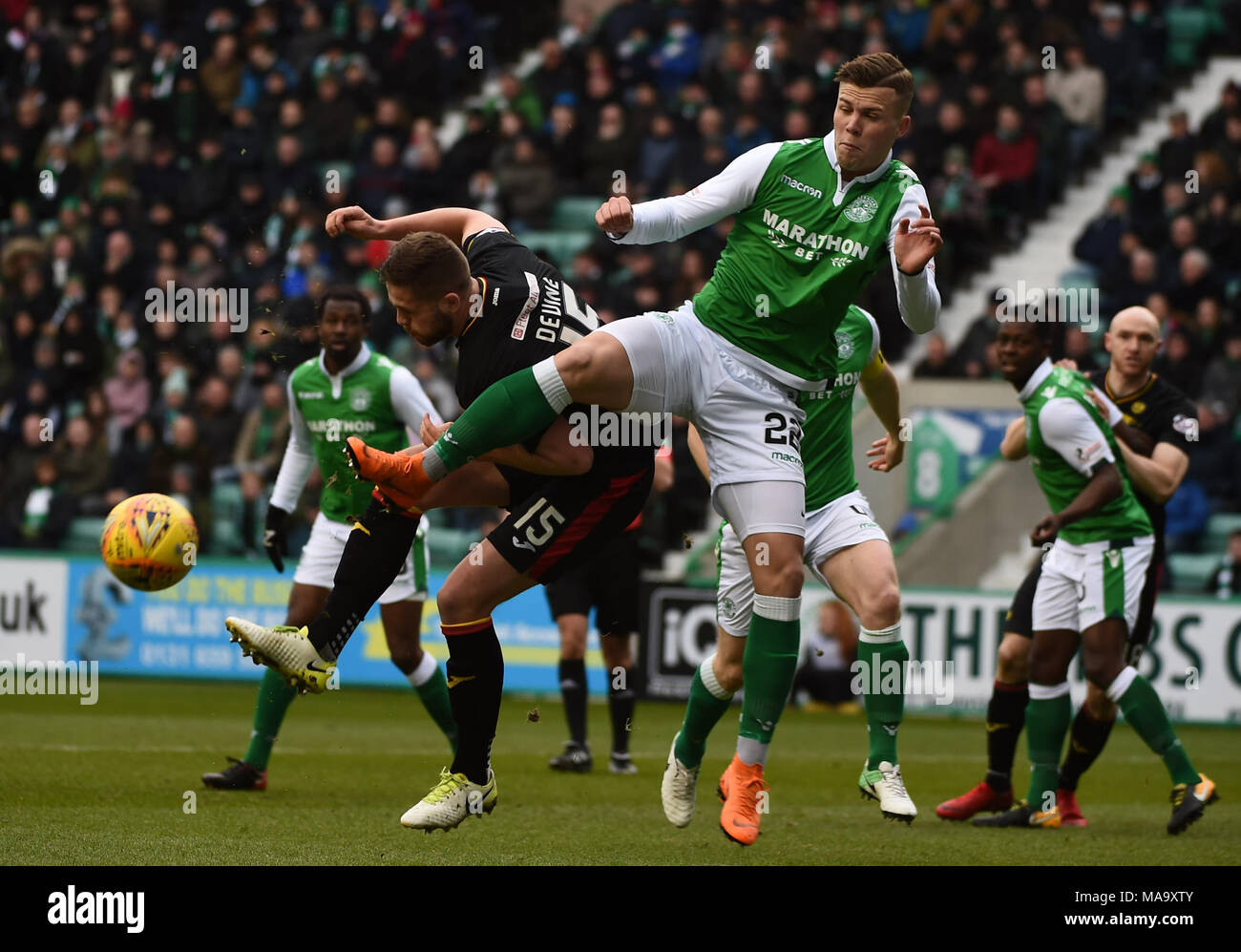 Scottish Premiereship, Hibernian v Partick Thistle, Edinburgh, Midlothian, UK. 31,03, 2018. Pic shows:  Partick Thistle defender, Daniel Devine, manages to clear the ball from the feet of Hibs' Florian Kamberi  during the Scottish Premiereship clash between Hibernian and Partick Thistle at Easter Road Stadium, Edinburgh.  Credit: Alamy/Ian Jacobs - Stock Image
