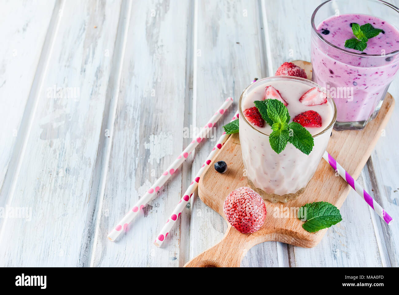Two refreshing Summer pink and purple smoothie or milkshake with mint, yogurt, blueberries and strawberries. in glass with ingredients, on white woode Stock Photo