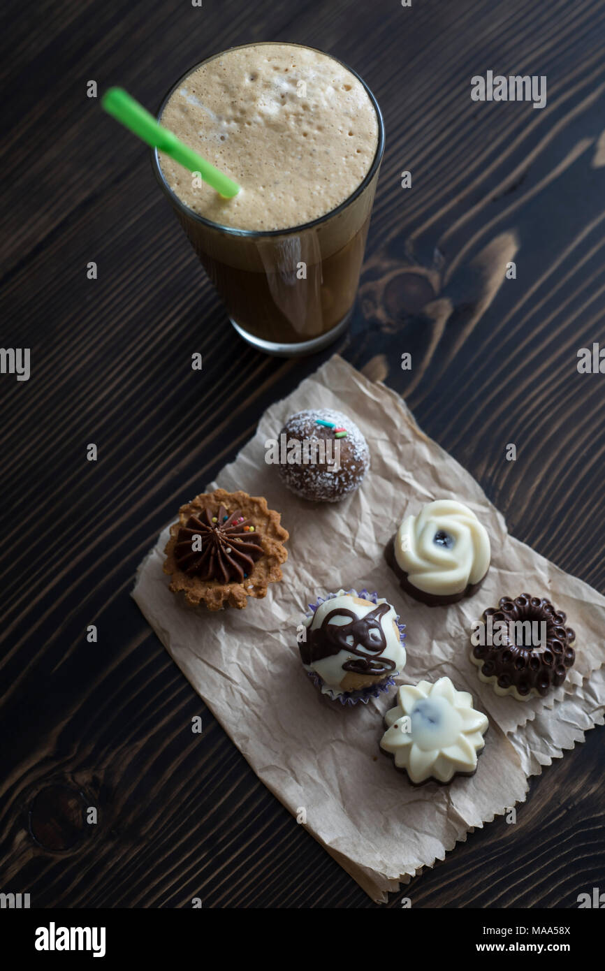 Coffee and small colorful sweet cakes, from above - Stock Image