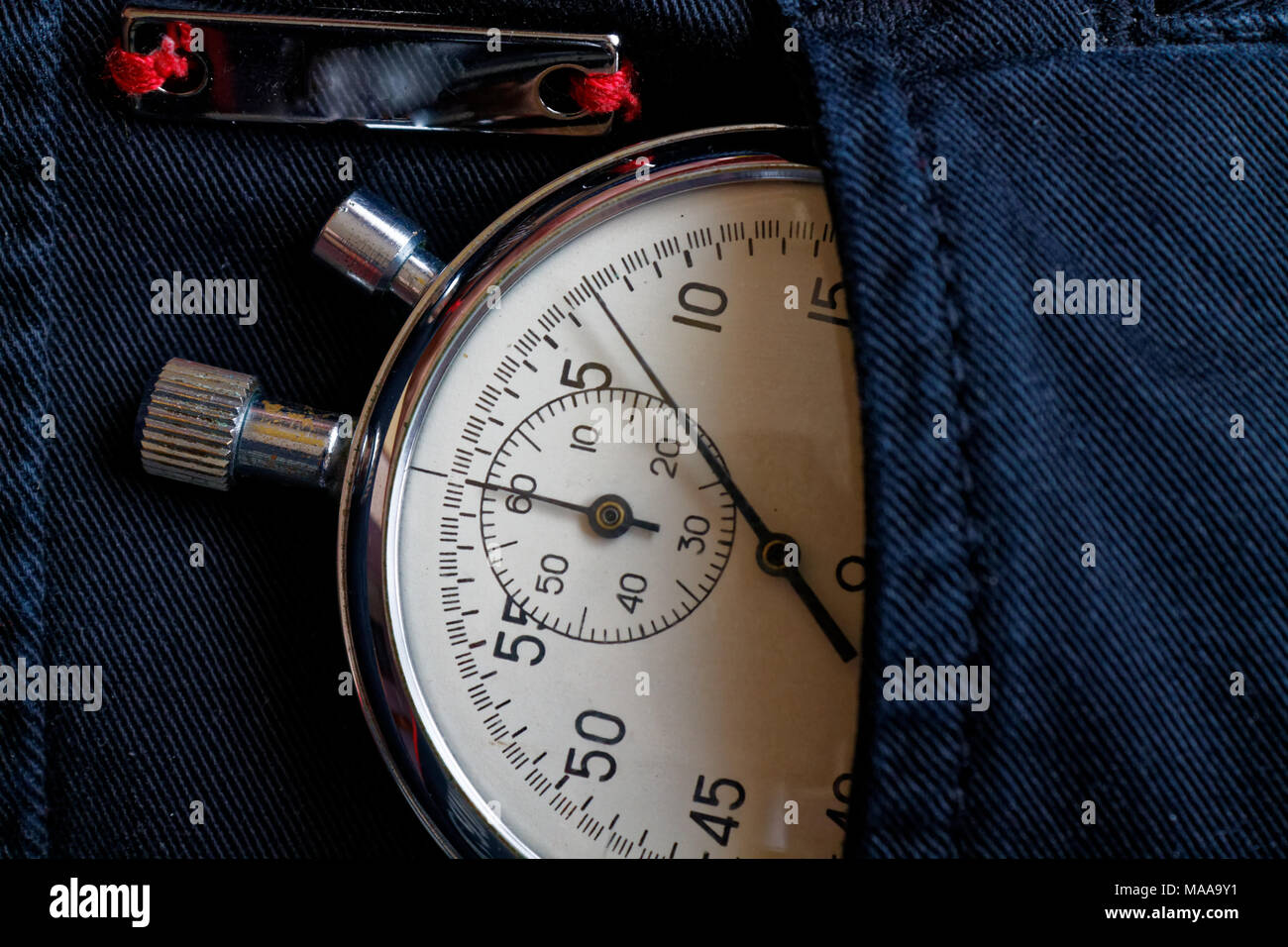Vintage antiques Stopwatch, in black denim pocket with reflection plank, value measure time, old clock arrow minute, second accuracy timer record - Stock Image