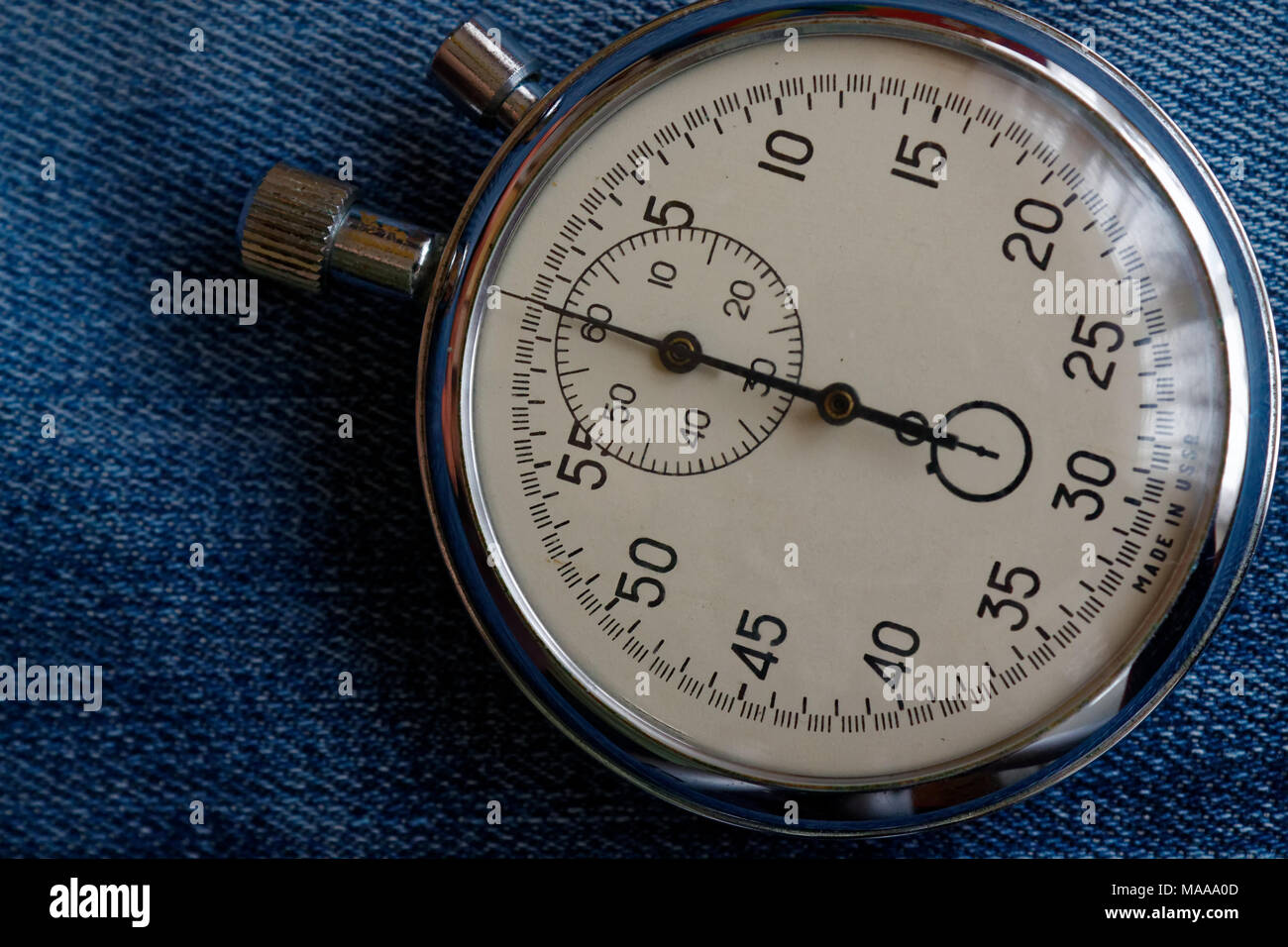 Stopwatch on worn blue jeans background, value measure time