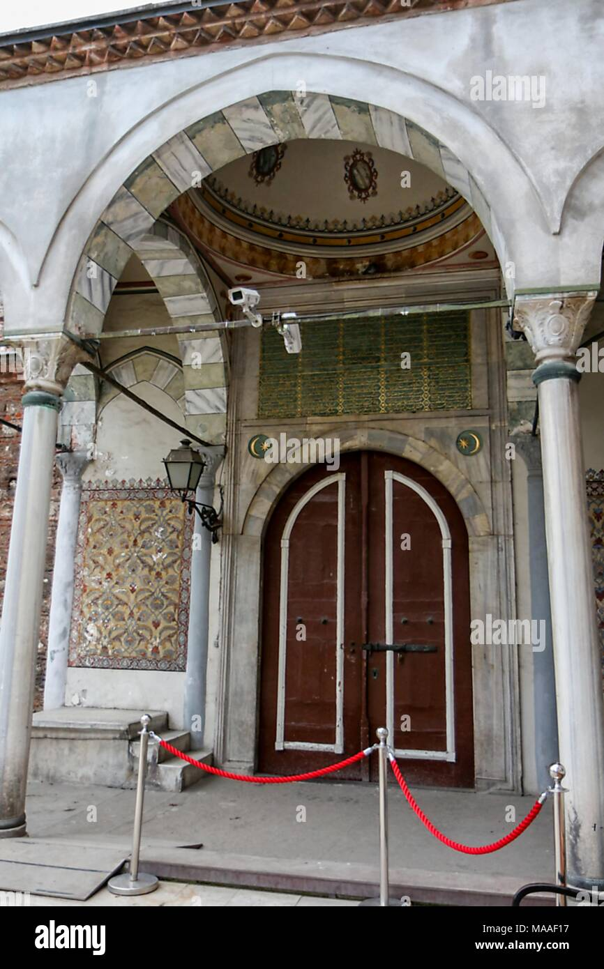Exterior view, from a low angle, showing the Ottoman style, arched and domed entrance portico, with Corinthian columns, multi-colored tilework, bench, and large arched doors leading into the Aya Irini (Hagia Irene), a former Greek Eastern Orthodox church, now used as a museum and concert hall, located in the outer courtyard of Topkapi Palace in Istanbul, Turkey, November 16, 2017. () - Stock Image