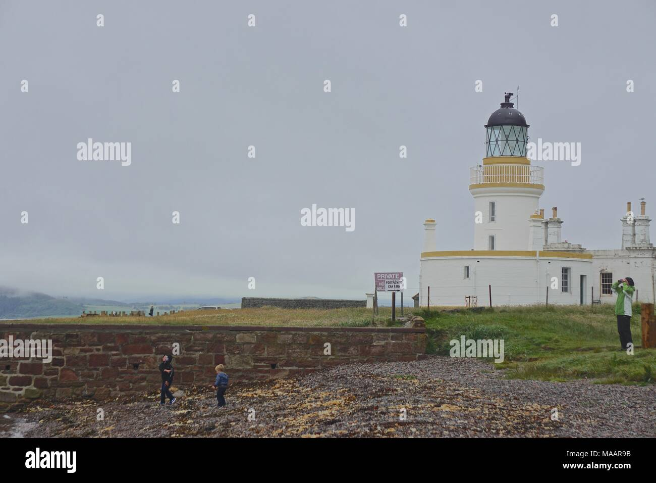 A family at the Chanonry Point Lighthouse (1846) on the Black Isle, Scotland, a popular location for dolphin watching in the Moray Firth. - Stock Image