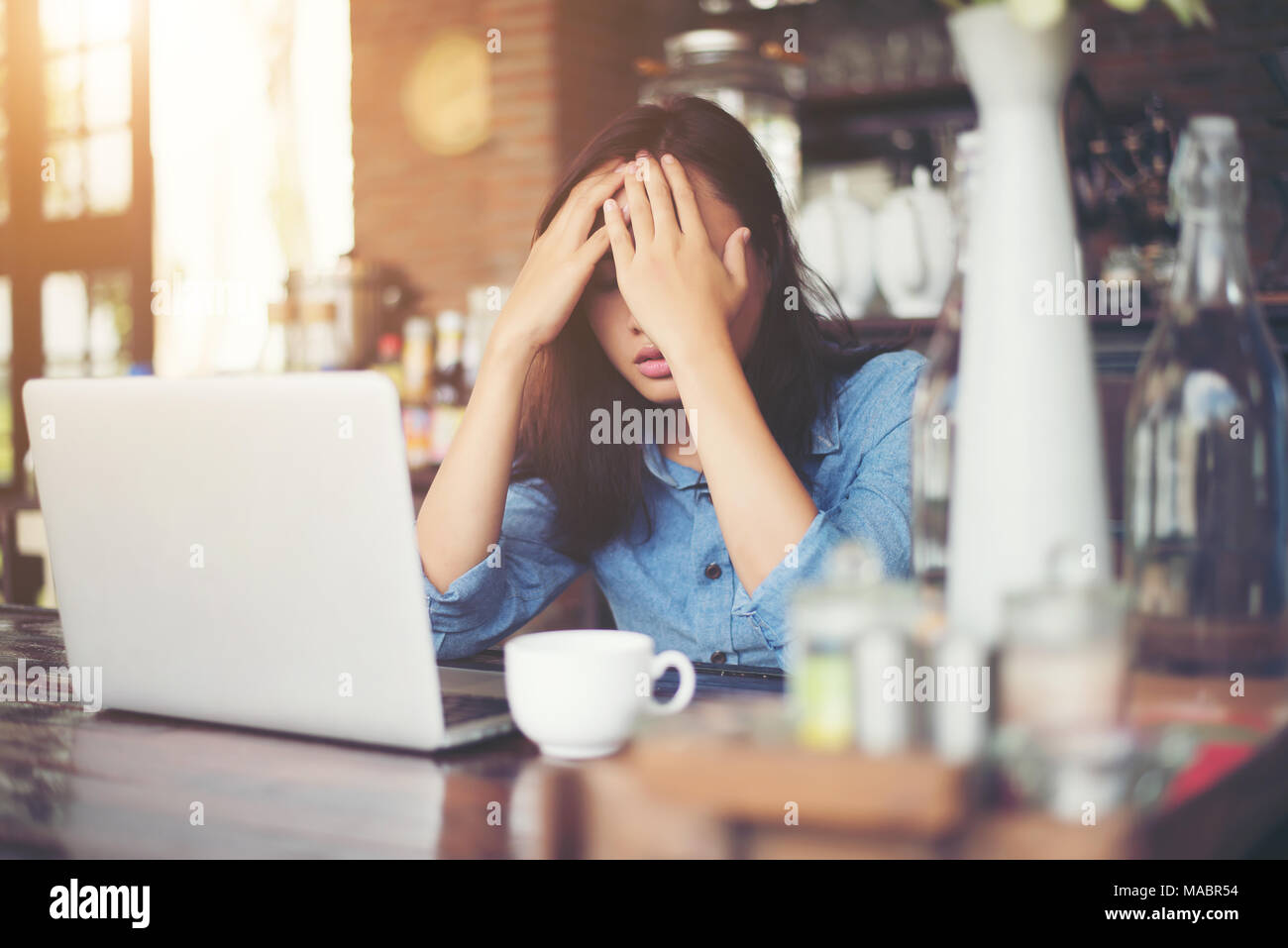 Young woman sitting in a cafe with her laptop, Stressful for work. - Stock Image