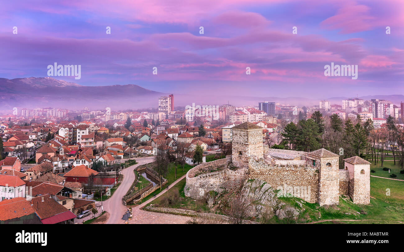 Magenta sunset view of misty city with a foreground ancient fortress and distant summit covered in snow - Stock Image