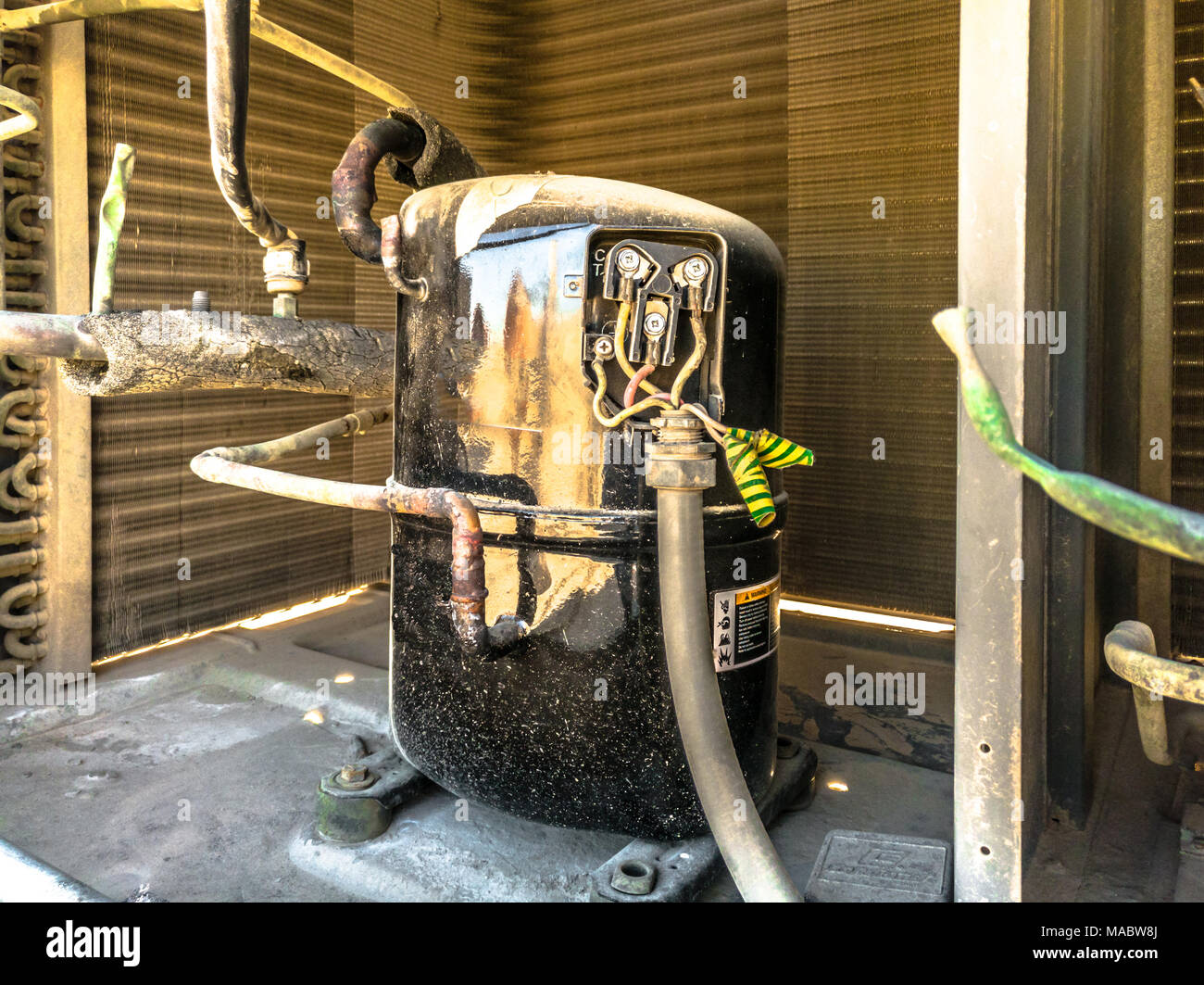 closeup of a shining compressor after cleaning service fixed into a heavy duty air conditioning system kept on the roof it was serviced by professiona - Stock Image