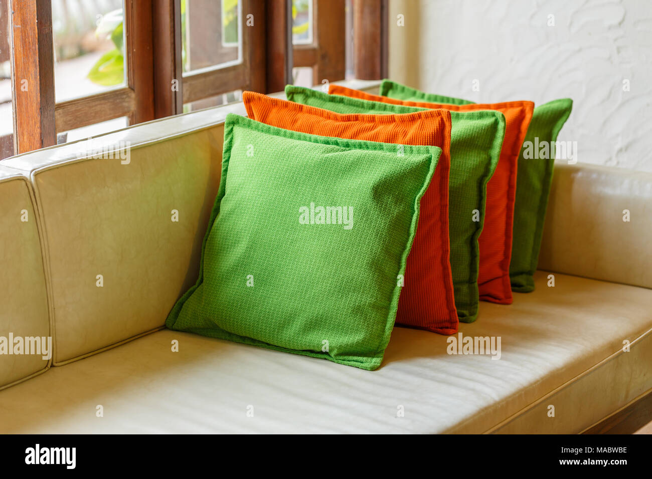 Green And Red Decorative Pillows On White Leather Sofa Stock Photo Alamy