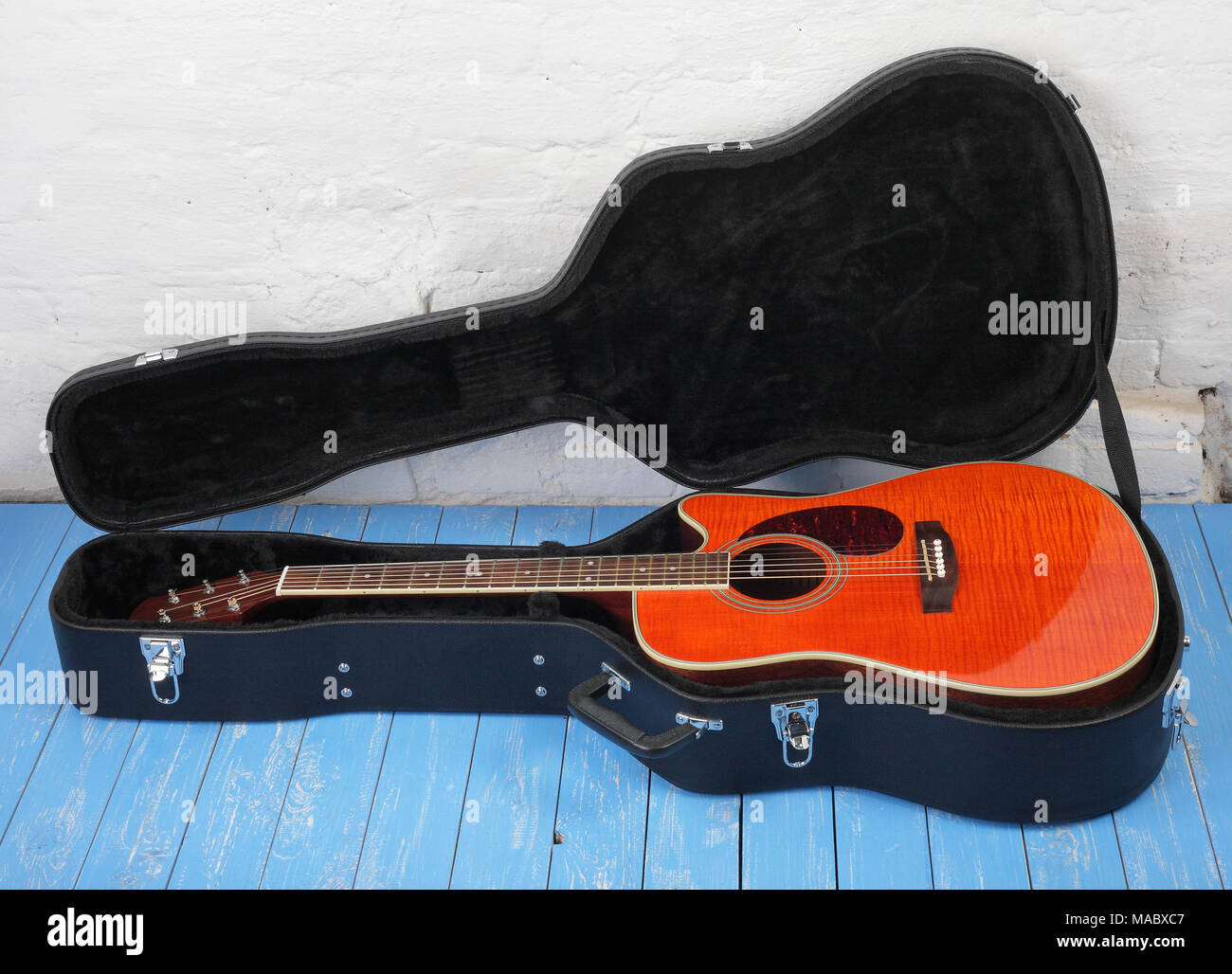 Musical instrument - Orange flame maple, acoustic guitar in hard case on a blue wood, and white brock wall background. Stock Photo