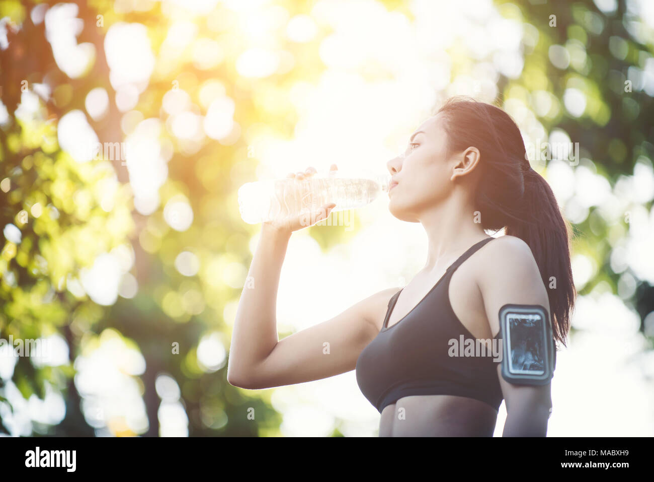 Fitness woman athlete takes a break, Drinking water, Hot day. Country rural road nature background. - Stock Image