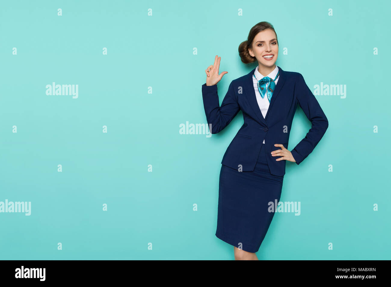 Happy stewardess in blue formal wear is showing pistol hand sign, smiling and looking at camera. Three quarter length studio shot on turquoise backgro - Stock Image