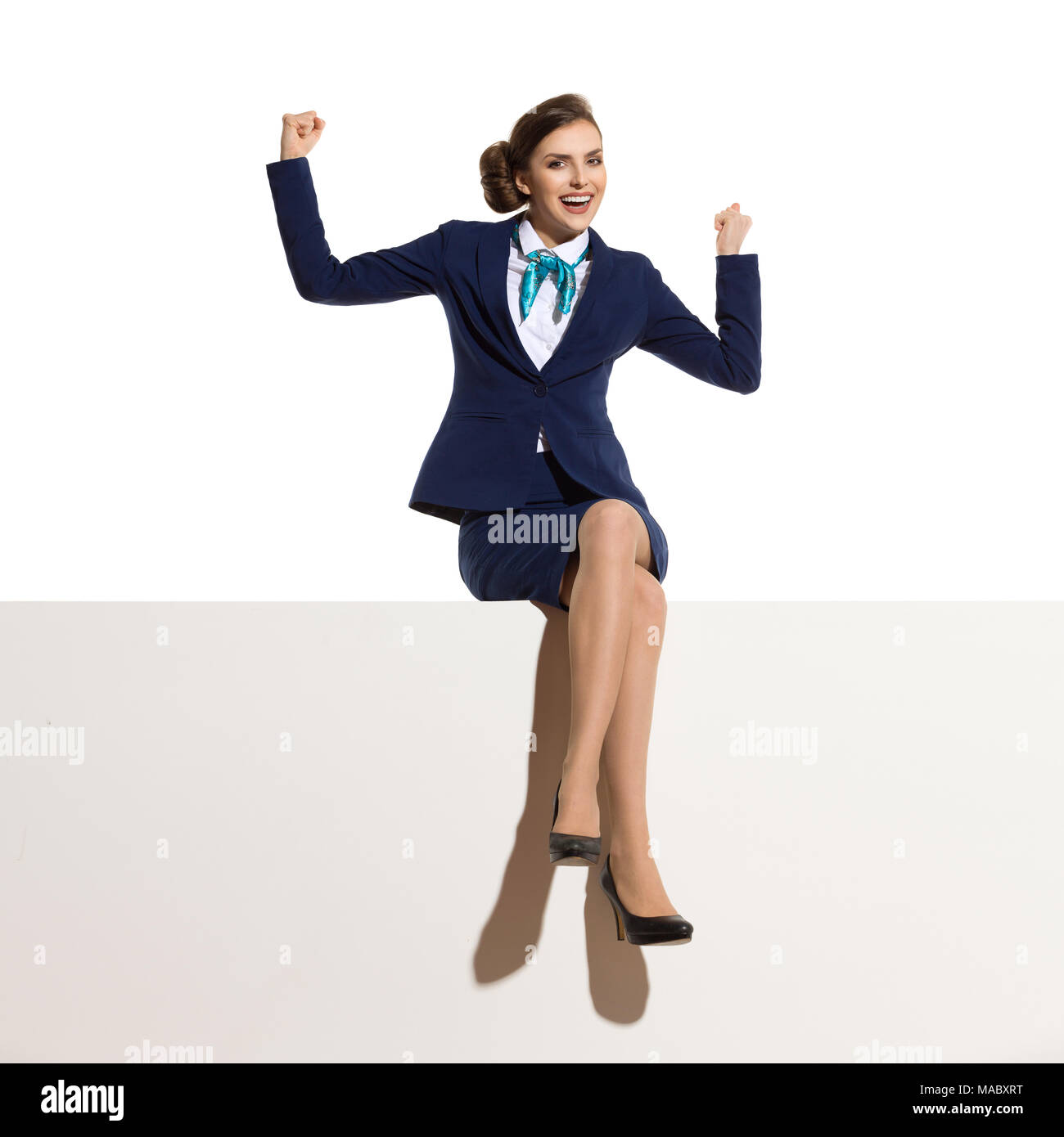 Businesswoman in blue suit and black high heels is sitting on a top with legs crossed, flexing muscles, smiling and looking at camera. Full length stu - Stock Image