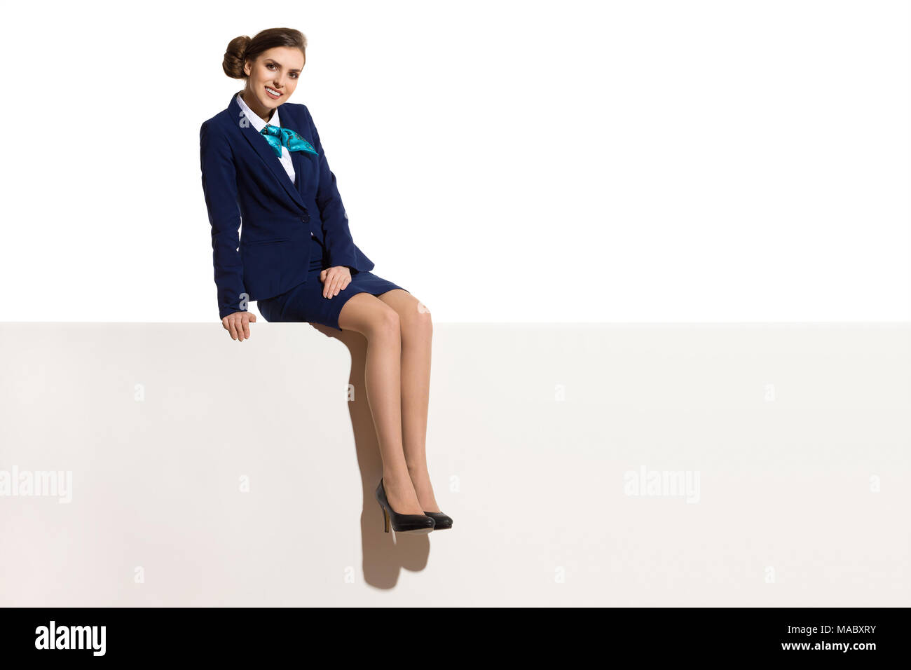 Businesswoman in blue suit and black high heels is sitting on a top of a white banner and smiling. Full length studio shot. - Stock Image