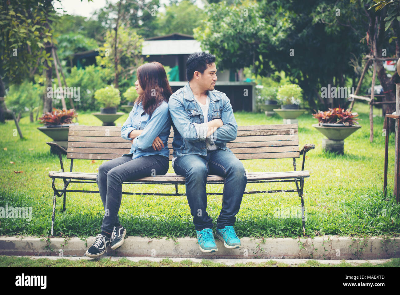 Displeased young couple sitting on bench in park, Couple lifestyle concept. - Stock Image