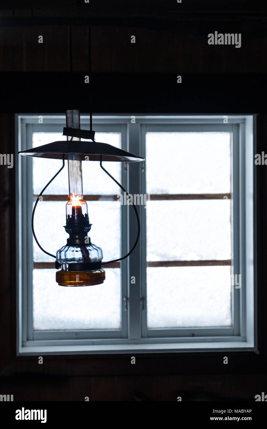 An oil lamp burning with a cabin window behind, Norway - Stock Image
