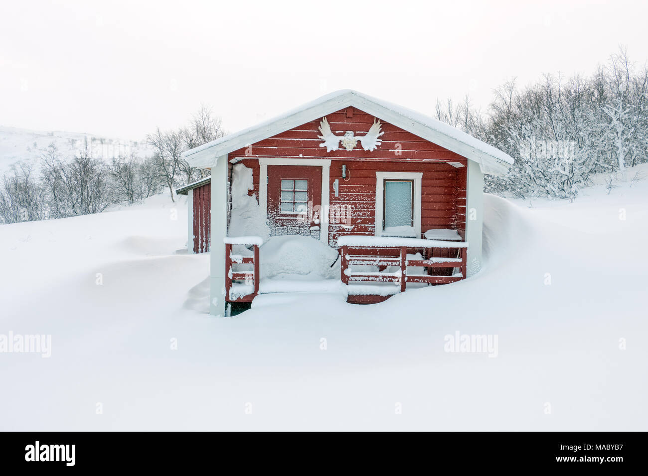 Snow covered cabin in a Sami village in Swedish Lapland - Stock Image