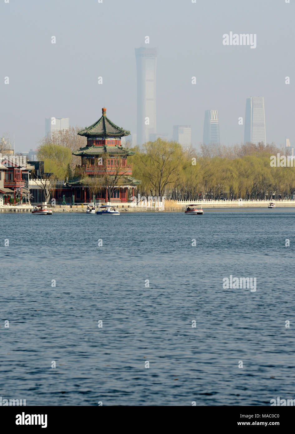 View of a pavilion in Shichahai scenic area in Houhai, with the outline of buildings of the CBD visible in the distance behind. Beijing, China - Stock Image