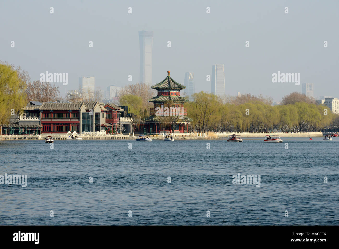 View of a pavilion in Shichahai scenic area in Houhai, with the outline of buildings of the CBD visible in the distance behind. Beijing, China Stock Photo