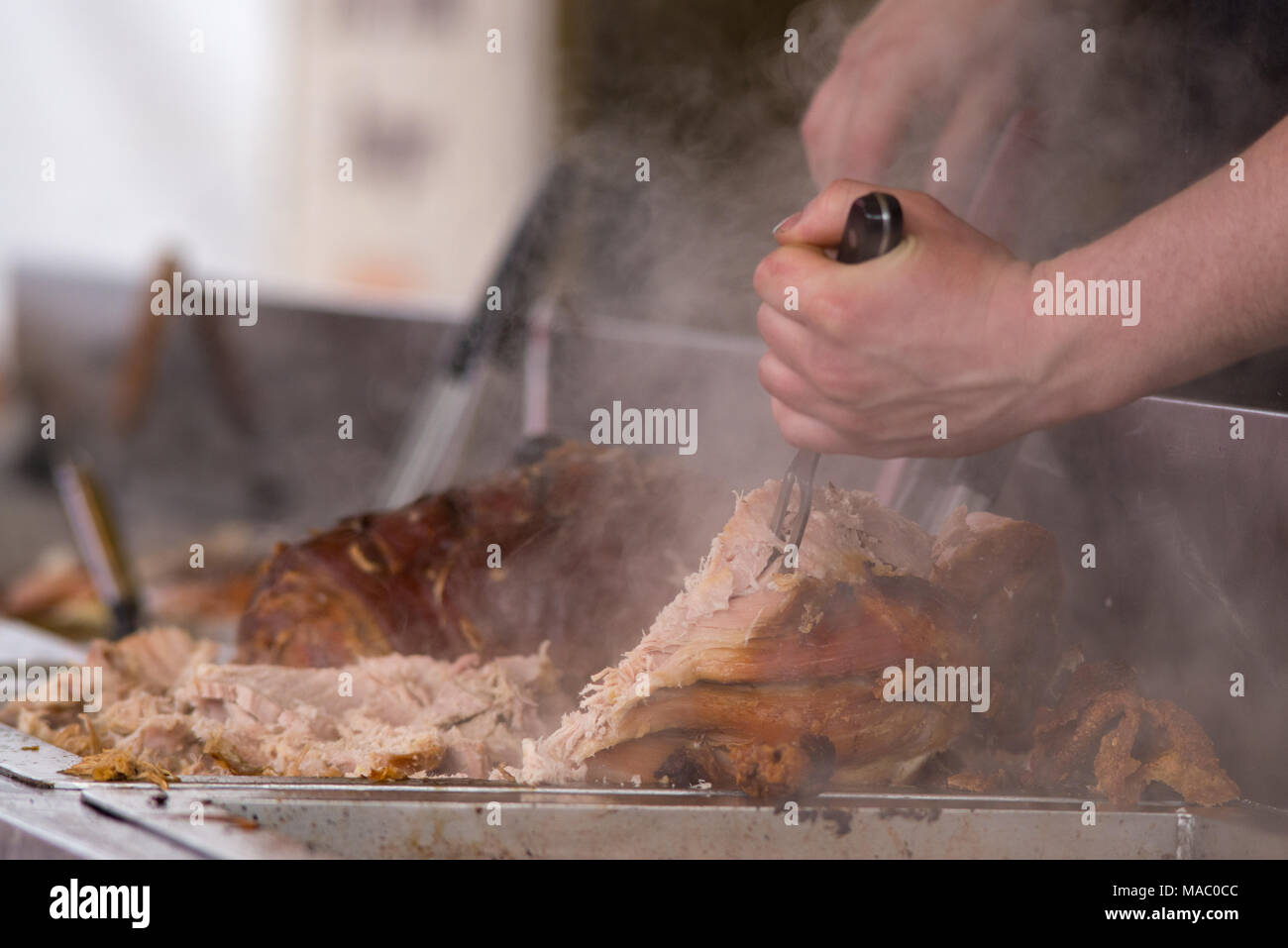 man carving pork joint with fork and knife at hog roast - Stock Image
