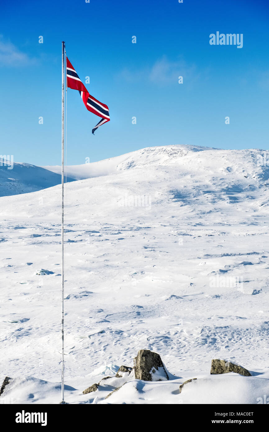 A Norwegian flag flying from flagpole in winter mountains - Stock Image